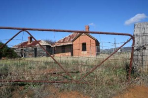 rusted gate and derelict house